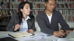 Um jovem casal asiático, homem e mulher, discutindo projeto na biblioteca video estoque