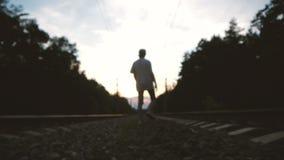 Um jovem desocupado caminha no meio de uma trilha ferroviária no pôr do sol video estoque
