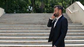 Um jovem empresário atrativo com barba em uma camisa e uma jaqueta caminha de bom humor no parque passando pelas escadas e fala s vídeos de arquivo
