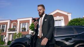 Um jovem empresário caucasiano bonitão de terno formal com gravata sai do carro preto e aceita um telefone importante filme