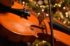 Um jovem que joga o violino com uma árvore de Chrismas no fundo fotografia de stock royalty free