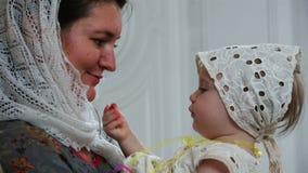 Um jovem sere de mãe a jogos com seu bebê que guarda o em seus braços filme