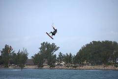 Um Kitesurfer crescente acima no ar rebocado por um papagaio obrigatório Imagens de Stock