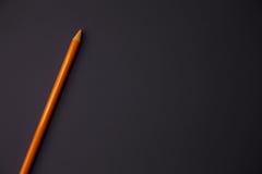 Um lápis alaranjado no fundo roxo imagens de stock
