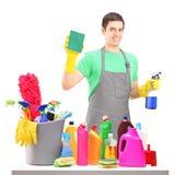 Um líquido de limpeza masculino de sorriso com equipamento da limpeza Imagem de Stock