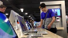 Um lado do computador de tentativa de Macbook da exposição dos povos vídeos de arquivo