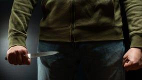 Um ladrão com uma faca grande - um assassino do afiado-assassino aproximadamente para cometer o assassinato, extorsão, roubo Arti fotografia de stock royalty free
