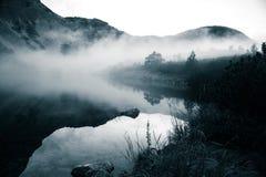 Um lago bonito da montanha em uma névoa em Tatry, Eslováquia imagem de stock