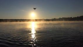 Um lago bonito no por do sol e um zangão que voa sobre ele no slo-mo filme