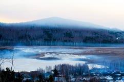 Um lago com uma montanha no fundo foto de stock