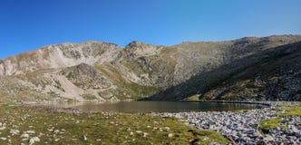 Um lago da água calma entre as montanhas Imagens de Stock