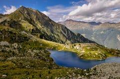 Um lago da montanha em um período do sol Foto de Stock