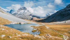 Um lago da montanha no outono com as montanhas cobertas com a neve no fundo Foto de Stock