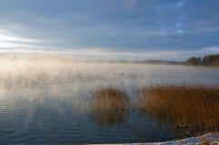 Um lago está na névoa Fotos de Stock