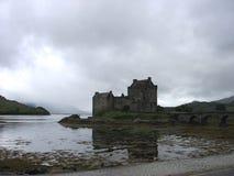 Um lago reflete uma imagem do castelo e da ponte de Eilean Donan nas montanhas de Escócia, Reino Unido Fotografia de Stock