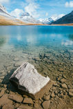 Um lago transparente da montanha com uma rocha Fotos de Stock