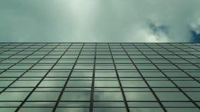 Um lapso de tempo com uma construção incorporada que reflete as nuvens ao meio do quadro filme