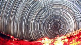 Um lapso de tempo de uma noite estrelado com uma sombra de uma árvore no primeiro plano e com um efeito da fuga da estrela vídeos de arquivo
