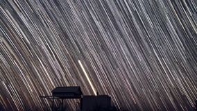 Um lapso de tempo de uma noite estrelado com uma sombra de uma árvore no primeiro plano e com um efeito da fuga da estrela filme