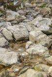 Um leito fluvial com rochas grandes Foto de Stock