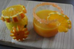 Um limão e um vidro do suco de laranja com uma borda do açúcar da cenoura e de fatias alaranjadas em um fundo de madeira claro Fotos de Stock