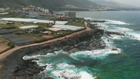 Um litoral longo da areia preta e dos penhascos compostos da lava vulcânica congelada, vista aérea Tenerife, Ilhas Can?rias, Spai video estoque