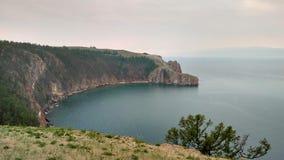 Um litoral rochoso alto um penhasco no mar um lago e uma névoa sobre a água foto de stock royalty free