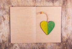 Um livro aberto com folhas vazias e um marcador de madeira Pendente de madeira na forma do coração Fotos de Stock Royalty Free