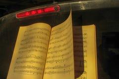 Um livro aberto de contagens velhas da música ao lado de um sinal vermelho em um fundo preto foto de stock