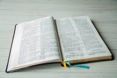 Um livro aberto em uma tabela de madeira A Bíblia no fundo de madeira imagens de stock