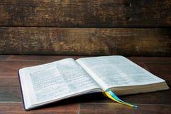 Um livro aberto em uma tabela de madeira A Bíblia no fundo de madeira imagens de stock royalty free