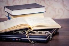 Um livro aberto está encontrando-se em um portátil que seja ligado por uma corrente Livros em vez dos computadores Amor ao read_ fotos de stock royalty free