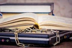 Um livro aberto est? encontrando-se em um port?til que seja ligado por uma corrente Livros em vez dos computadores Amor ao read_ fotografia de stock royalty free