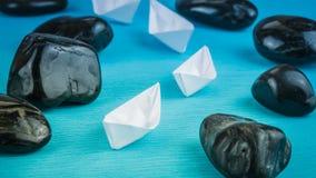 Um Livro Branco mais adicional da ligação da liderança envia entre pedras no fundo azul Fotografia de Stock Royalty Free