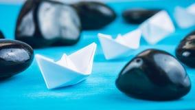 Um Livro Branco mais adicional da ligação da liderança envia entre pedras no fundo azul Direita para a esquerda movendo-se Fotografia de Stock