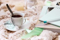 Um livro, um caderno, um copo do café preto, amendoins no açúcar, uma vela, uma estátua de um anjo do emplastro em uma cobertura  imagens de stock