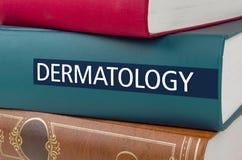Um livro com a dermatologia do título escrita na espinha imagem de stock