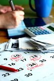 Um livro de cheques, contas, uma calculadora, um calendário e uma escrita da pessoa em um livro de cheques imagens de stock