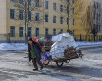 Um lixo levando do homem na rua imagens de stock