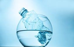 Um lixo plástico da garrafa na água em um aquário, com um fundo azul O conceito de manter a sustentabilidade ambiental fotografia de stock