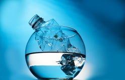 Um lixo plástico da garrafa na água em um aquário, com um fundo azul O conceito de manter a sustentabilidade ambiental foto de stock royalty free