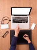 Um local de trabalho com dispositivos móveis, a tabuleta gráfica e uns vidros no fundo de madeira Imagem das mãos humanas usando  Fotografia de Stock Royalty Free