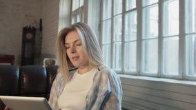 Um louro bonito comunica-se através da relação video através de uma tabuleta Uma jovem mulher está sentando-se no sofá e está fal video estoque