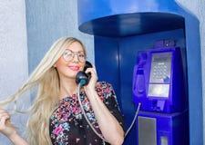 Um louro bonito nos vidros está guardando um receptor de telefone em um payphone Belamente sorrindo e falando no telefone foto de stock royalty free