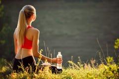 Um louro novo em uma parte superior vermelha e em umas calças pretas senta-se na grama na natureza Uma mulher desportiva está gua Foto de Stock Royalty Free