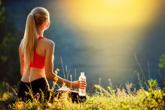 Um louro novo em uma parte superior vermelha e em umas calças pretas senta-se na grama na natureza Uma mulher desportiva está gua Imagem de Stock Royalty Free