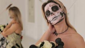 Um louro novo em um vestido preto e composição sob a forma de um esqueleto Halloween vídeos de arquivo
