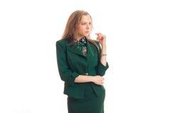Um louro novo encantador no vestido verde olha para Fotografia de Stock