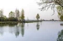 Um lugar para suportes meditação-de madeira do miradouro na costa do lago perto das árvores novas imagem de stock royalty free