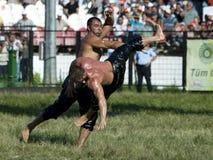 Um lutador pesado é lanç no ar por seu oponente no festival turco da luta romana do óleo de Kirkpinar em Edirne em Turquia Imagens de Stock Royalty Free